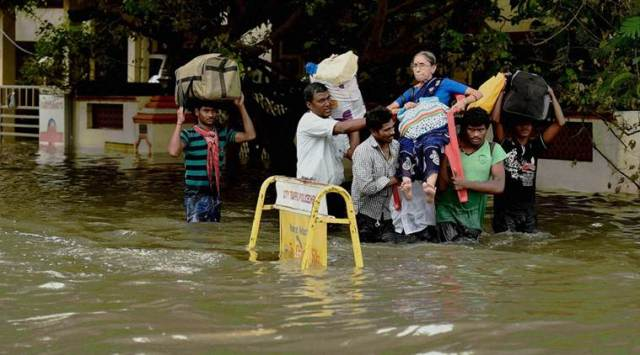 Chennai: An older woman lifted by rescue worker following heavy rains, in Chennai on Monday. PTI Photo(PTI11_16_2015_000203B)