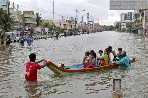 People travel on a boat as they move to safer places through a flooded road in Chennai, December 2, 2015. REUTERS/Stringer